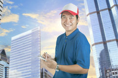 Toothy smiling face of delivery man and smart computer in hand p. Reparing for taking customer order isolated whtie background Royalty Free Stock Image