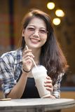 Toothy smiling face happiness emotion of younger asian woman wit. H cool drink bottle in hand Royalty Free Stock Images