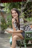 Toothy smiling face of younger asian woman with smart phone in h. And sitting in green park Stock Image