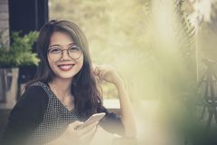 Toothy smiling face of younger asian woman with smart phone in h stock photography