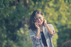 Toothy smiling face of younger asian woman talking on mobile phone in green park stock photos