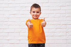 Toothy smiling handsome boy holding thumbs-up Stock Photos