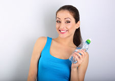 Toothy smiling happy beautiful woman holding the bottle of pure Stock Photos