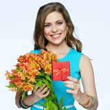 Toothy smiling happy woman holding flower with gift box. White background isolated portrait Stock Photography