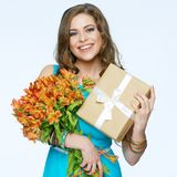Toothy smiling happy woman holding flower with gift box. White background isolated portrait Royalty Free Stock Image