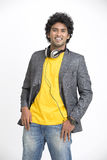 Toothy smiling Indian young urban man standing with headphone Royalty Free Stock Photos