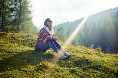 Toothy smiling woman basking on sun rays of the sun. Side low angle shot of happy Caucasian woman who is sitting on the grass on the mountain peak and looking at Royalty Free Stock Photo