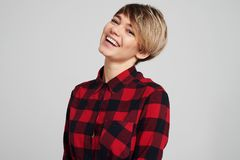 Toothy smiling woman in checked shirt looking at camera stock image