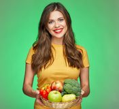 Toothy smiling woman holding straw basket with healthy food. Vegetabless and fruits Stock Photography
