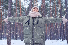 Toothy smiling woman with spread hands looking at the sky. Low angle of happy and smiling woman looking at the sky while standing in the forest. Winter is coming Royalty Free Stock Image