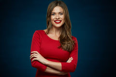 Toothy smiling woman wearing red dress with crossed arms. Against dark blue background Stock Image