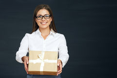 Toothy smiling young business woman hold present box. Black studio background Stock Images