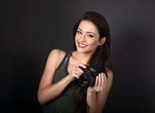 Toothy smiling young female photograph holding camera and lookin Royalty Free Stock Photos
