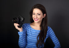 Toothy smiling young female photograph holding camera and lookin Royalty Free Stock Photography