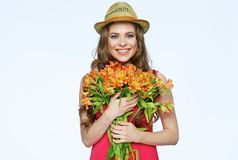 Toothy smiling young woman with bouquet  spring flowers. Isolated white background Royalty Free Stock Photo
