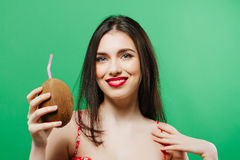 Toothy Smiling Young Woman with Cocktail in Hand on Green Background. Portrait of Brunette with Red Sensual Lips Posing in Studio and Looking at the Camera Stock Image