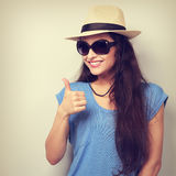 Toothy smiling young woman in summer hat and sun glasses showing Stock Image