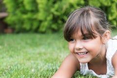 Toothy uśmiechnięta twarz małej dziewczynki lying on the beach na trawie Zdjęcie Royalty Free