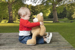 Tootler playing with her teddy bear, outdoors Stock Photo