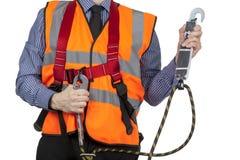 Topógrafo da construção na veste alaranjada da visibilidade que fixa a correia do chicote de fios de segurança Foto de Stock