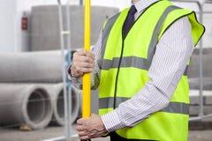 Topógrafo da construção na visibilidade alta que ajusta o suporte do tripé Fotografia de Stock Royalty Free