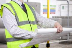 Topógrafo da construção na visibilidade alta que inspeciona o pla da construção Fotos de Stock Royalty Free