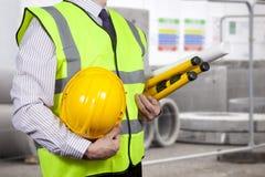 Topógrafo da construção na visibilidade alta que leva um tripé Fotografia de Stock Royalty Free