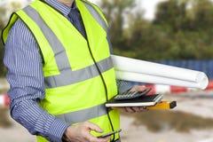Topógrafo da construção olá! no vis que leva plantas e calculadora do local Fotos de Stock