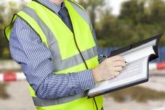 Topógrafo da construção olá! no vis que verifica dados no dobrador do local Fotografia de Stock Royalty Free