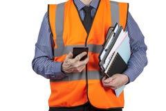 Topógrafo del edificio en carpetas que llevan y teléfono del chaleco anaranjado de la visibilidad Imagenes de archivo