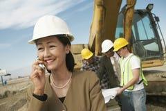 Topógrafo en el casco de protección en Front Of Workers Using Cellphone en sitio fotos de archivo