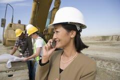 Topógrafo en el casco de protección en Front Of Workers Using Cellphone en sitio foto de archivo libre de regalías