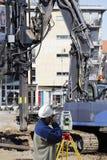 Topógrafo que mede o grande terreno de construção interno Imagem de Stock Royalty Free