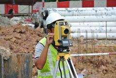 Topógrafo que usa el equipo de la encuesta en el emplazamiento de la obra Foto de archivo libre de regalías