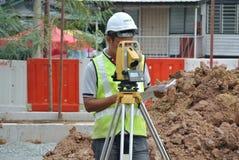 Topógrafo que usa el equipo de la encuesta en el emplazamiento de la obra Foto de archivo