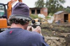 Topógrafo que usa el teodolito en sitio imagenes de archivo