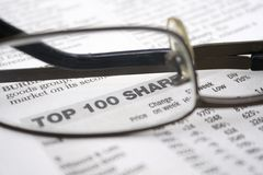 Top 100 Shares. A pair of glasses on a stock trade news paper Royalty Free Stock Photography