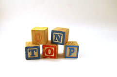 On Top. Toy blocks with text reading 'on top' blockes are scuffed and scarred like going through a rough time royalty free stock images