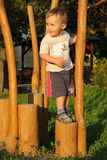 On the top. Little child standing on the top of a step in a playground, adhering to a wooden column Royalty Free Stock Photos