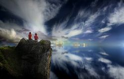 At the top. Two people sit atop a high cliff, overlooking a dramatic view of the sky and the clouds Stock Photos