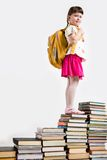 On the top. Intelligent schoolgirl standing on top of book pile and looking at camera Stock Photo