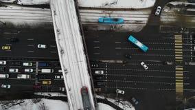 Top aéreo abajo de la vista del atasco en un camino del invierno con muchos coches y autobuses, tranvía azul y tren gris en el fe metrajes