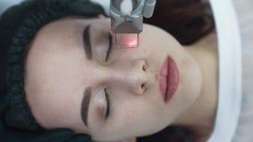 Top abajo de la cara de la visión de la mujer joven en el procedimiento de peladura facial del laser, cámara lenta almacen de metraje de vídeo