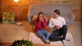 Top abajo de la opinión dos amigos jovenes que se sientan en la alfombra y las bebidas calientes de consumición que comunica en a almacen de video