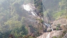 Top abajo de la vista aérea de la cascada gigante que fluye en las montañas de Vietnam filmadas en la cámara lenta almacen de video