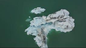 Top abajo de la vista aérea de los icebergs del glaciar que flotan en laguna en Islandia metrajes