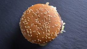 Top abajo del lanzamiento del cheeseburger doble apetitoso con sésamo en los bollos que giran en el movimiento almacen de metraje de vídeo