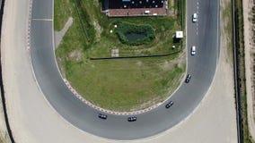 Top abajo del vídeo aéreo video 4k de la conducción de automóviles a través de esquina en el circuito de carreras Zandvoort del d almacen de metraje de vídeo
