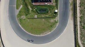 Top abajo del vídeo aéreo video 4k de los coches que derivan a través de esquina en el circuito de carreras Zandvoort del deporte almacen de metraje de vídeo