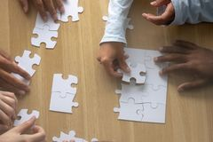 Top above close up view multiracial human hands assembling puzzle. Together on desk. Good teamwork and successful partnership, help and support, search right stock images